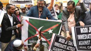 Members of All India Muslim Unity Front burn Pakistani flag during a protest against the Pulwama terror attack