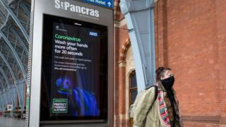 in_pictures A woman leaving St Pancras International station wearing a mask