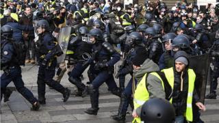 """La police tente de contrôler des manifestants """"gilets jaunes"""", près de l'Arc de Triomphe, à Paris."""