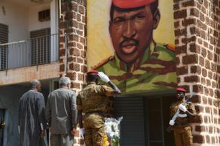 Burkina Faso's President Roch Marc Christian Kabore (left) and Ghana's former President Jerry Rawlings (centre) stand under the portrait of Burkina Faso's former President Thomas Sankara at the entrance of the house where he was killed in 1987, during the inauguration of his memorial at the Conseil de l'Entente in Ouagadougou.