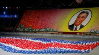 Performers holding up coloured boards creating a huge portrait of Kim Il-sung