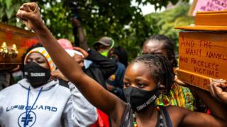 """Cosmas Mutethia""""s wife (R) wears a mask with her husband""""s name, who was killed by Kenyan Police during a night curfew, as she carries an empty coffin during their protest against police brutality in front of the Kenyan Parliament in Nairobi on June 9, 2020."""
