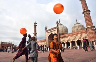 Hindistanlı uşaqlar narıncı şarlarla oynayır