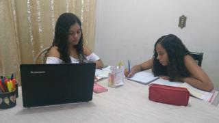 Irmãs Emily e Camila estudando em casa