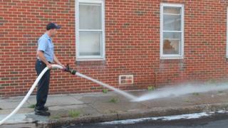 Un bombero de Baltimore lava la sangre que dejó en una acera uno de los homicidios ocurridos el sábado.