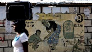 Una mujer pasa delante de un anuncio de Oxfam en Puerto Príncipe, Haití.