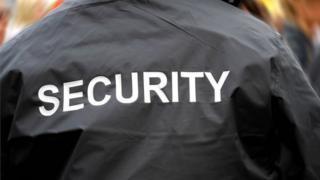 Pesin wey wear jacket wit security ontop.