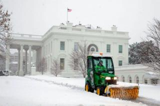 A vehicle clears snow to create a path next to the White House