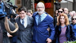 John Jarratt (centre) with supporters after the verdict in Sydney on Friday