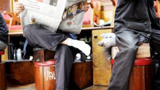 Homem lê jornal que mostra foto de Bolsonaro