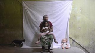 Retrato de mãe e filha congolesas que vivem em Ramos, na zona norte do Rio, ao lado do gato de estimação da família