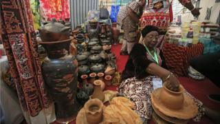 A woman makes clay pots during the opening ceremony of a tourism fair in Ivory Coast's main city of Abidjan on 27 April 2018