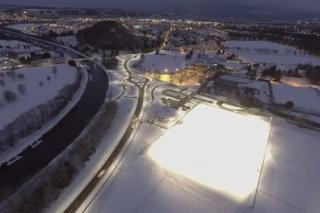 Aerial image of new road and lit up snow-covered rugby pitch