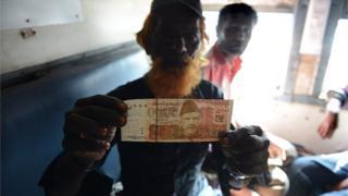 Indian fisherman displays a 5000 Pakistani rupee note