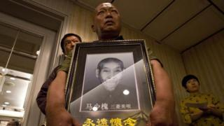 Ma Wenyi,holds a photo of his father who was forced to work during World War II at a mine for Mitsubishi Mining Corp