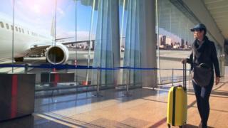 mulher carregando mala em aeroporto
