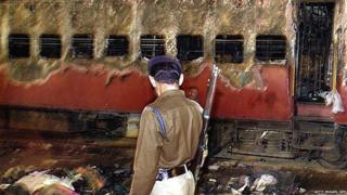 28 February 2002, an Indian policeman looks towards a burnt train coach and belongings of Hindu activists at Godhra Railway Station.