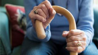Stock photo of elderly woman gripping a cane