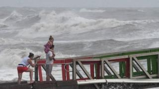 A girl covers her face from strong winds as her family members watch high swells from Hurricane Hanna from a jetty in Galveston, Texas