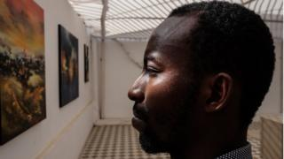 "Senegalese artist Baba Ly was one of dozens of artists to present at one of the Dakar Biennale's ""Off"" sites. Here he stands amid paintings from his series on urbanism."