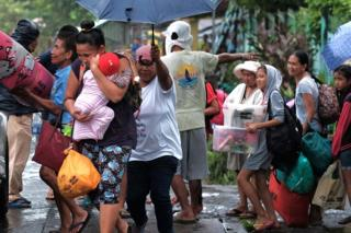 Villagers carry belongings as they are evacuated in anticipation of an approaching typhoon in Legaspi city, Albay province, Philippines, on 2 December 2019