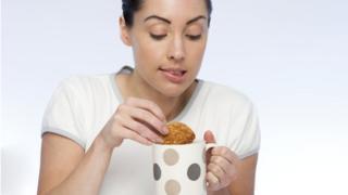 Woman dips biscuit in tea
