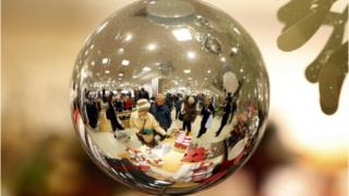 Christmas shoppers in John Lewis reflected through a glass ball