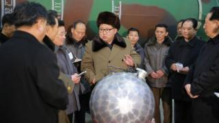 Kim Jong-Un talking with scientists and technicians alongside a mock-up of a nuclear bomb