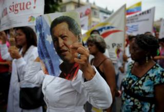 Una manifestante se cubre la cara con una careta del que fuera presidente de Venezuela, Hugo Chávez, en La Habana, Cuba, el 25 de agosto.
