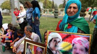 امرأة من إقليم كردستان تحمل صورة مسعود بارزاني عقب إعلان الأخير تنحيه عن منصب رئاسة الإقليم