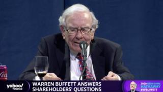 A screenshot of Warren Buffett speaking at the shareholders' meeting