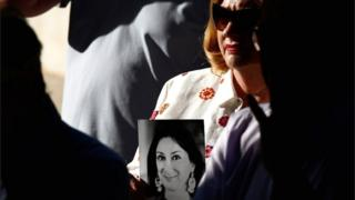 People hold up photos of anti-corruption journalist Daphne Caruana Galizia during a protest and vigil marking 21 months since her assassination, after three men were indicted for her murder, in Valletta, Malta, on 16 July 2019