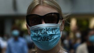 "A pro-democracy demonstrator wears a mask that reads ""suck it Carrie"" as she and others gather at Chater Garden"