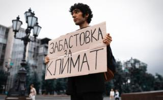 "Protester Arshak holds a sign reading ""climate strike"" in Moscow"