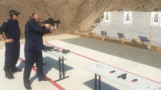 in_pictures New South Wales Police Minister David Elliott shooting at a target with a submachine gun at a prison's rifle range