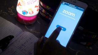 A student takes class online while using the Zoom app at her home