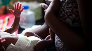 Une mère et son bébé portant une couche - archives