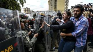 Venezuelan opposition deputy Amelia Belisario (C) argues with National Guard personnel in riot gear during a protest in front of the Supreme Court in Caracas on March 30, 2017.