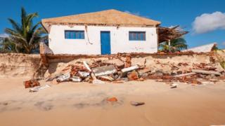 Foto da praia de Pititinga, em Natal, onde o avanço do mar diminuiu a faixa de areia e engoliu construções.