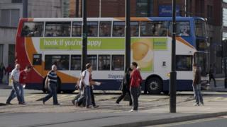 people walk on pavement with bus behind