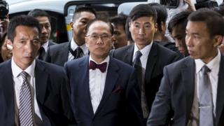 Former Hong Kong Chief Executive Donald Tsang (centre) is escorted by two policemen as he walks into the Eastern Law Court in Hong Kong