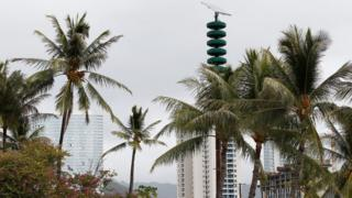 A tsunami warning tower in between palm trees at Kakaako Waterfront Park in Honolulu, Hawaii, November 28, 2017