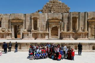 Prince William stands with Jordan's Crown Prince Hussein as they pose with people at the ancient city of Jerash, Jordan.