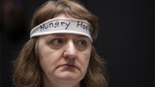 "A woman wearing a ""hungry hostage"" headband protests on Capitol Hill"
