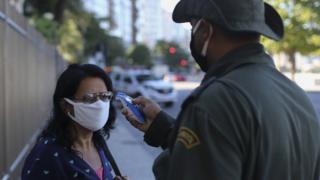 A member of the Municipal Civil Guard checks the temperature of a pedestrian in Brazil