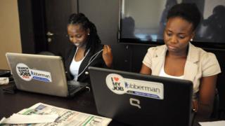 Two women dey look computer