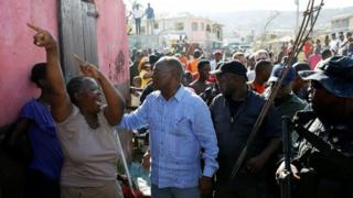 "A woman reacts as Haiti""s Interim President Jocelerme Privert (C) visits after Hurricane Matthew passes in Jeremie, Haiti, October 8, 2016"