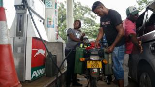 A petrol attendant serves a motorcyclist with two jerry cans attached to his motorbike at a fuel station,