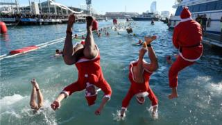 Participants in a Santa Claus costume jump into the water during the 110th edition of the