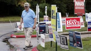 a voter walks past campaign signs